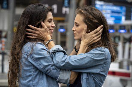Zdjęcie przedstawia dwie kobiety stojące na przeciwko siebie. Każda z nich ujmuje w dłonie twarz drugiej. Są podobne do siebie, mają długie brązowe oczy i jeansowe koszule.