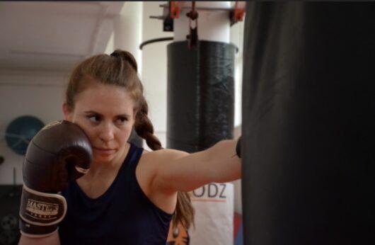 Zdjęcie przedstawia dziewczynę w rękawicach bokserskich która uderza w worek treningowy