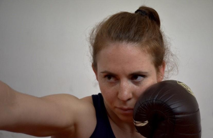 Zdjęcie przedstawia portret dziewczyny w rękawicach bokserskich z jedną ręką przysłaniającą twarz, a drugą wyprostowaną, jak podczas zadawania ciosu.