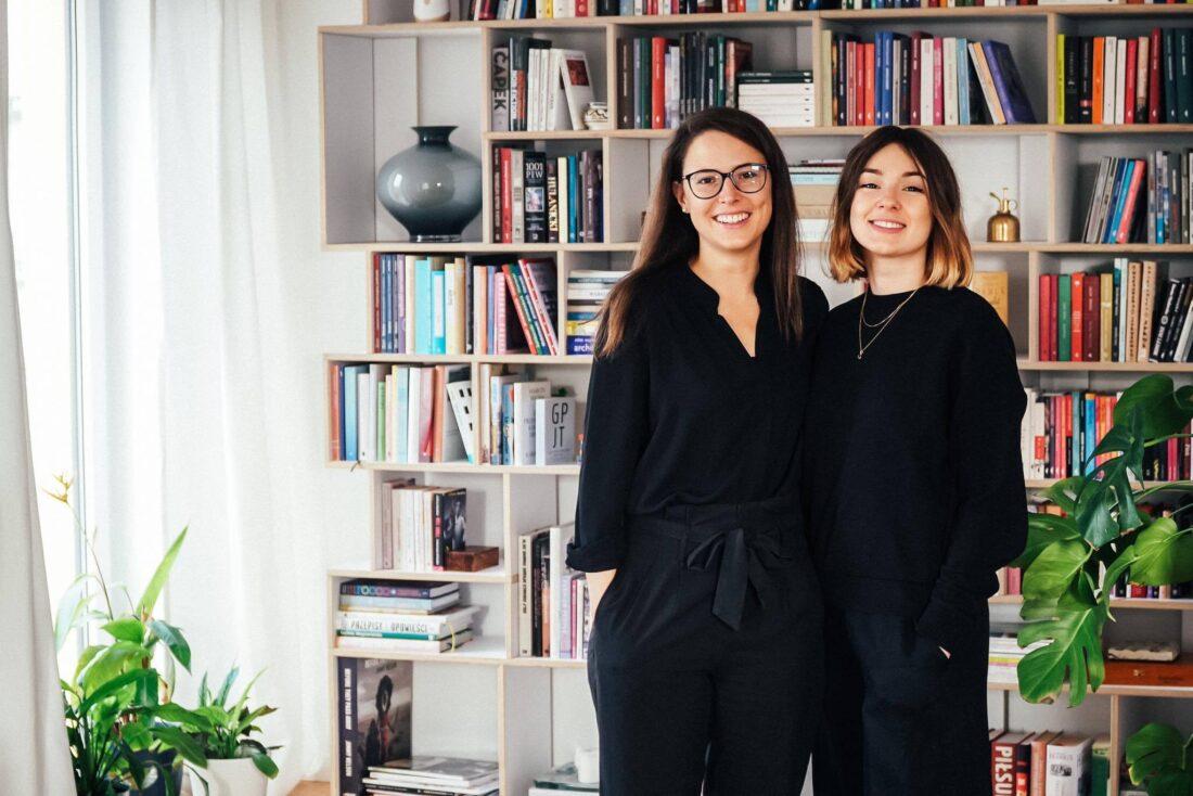 Zdjęcie przedstawia dwie uśmiechnięte młode kobiety - Natalie Pilling i Aleksandrę Bis - stojące na tle półki z książkami.